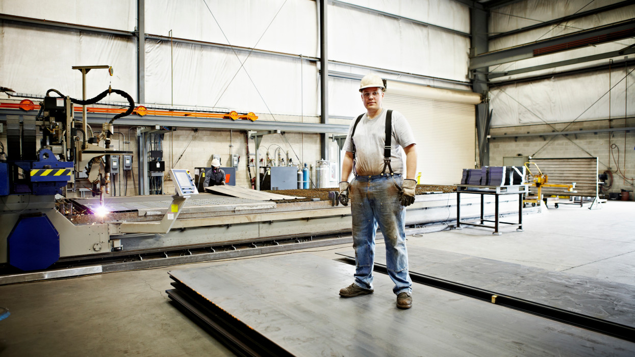 Steel worker standing on stack of sheets of steel smiling plasma cutter in background