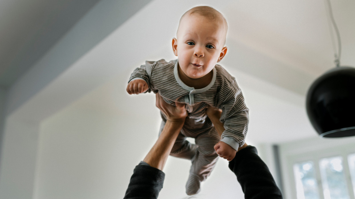 Close-up of father bonding with son. Father is lifting baby son into the air. Focus on baby.