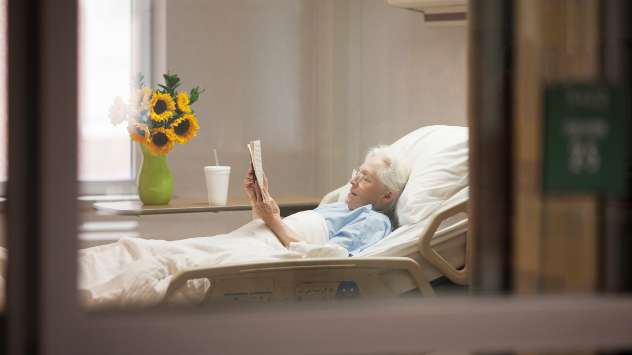 70s woman with glasses reading a book while lying in a hospital bed in her room