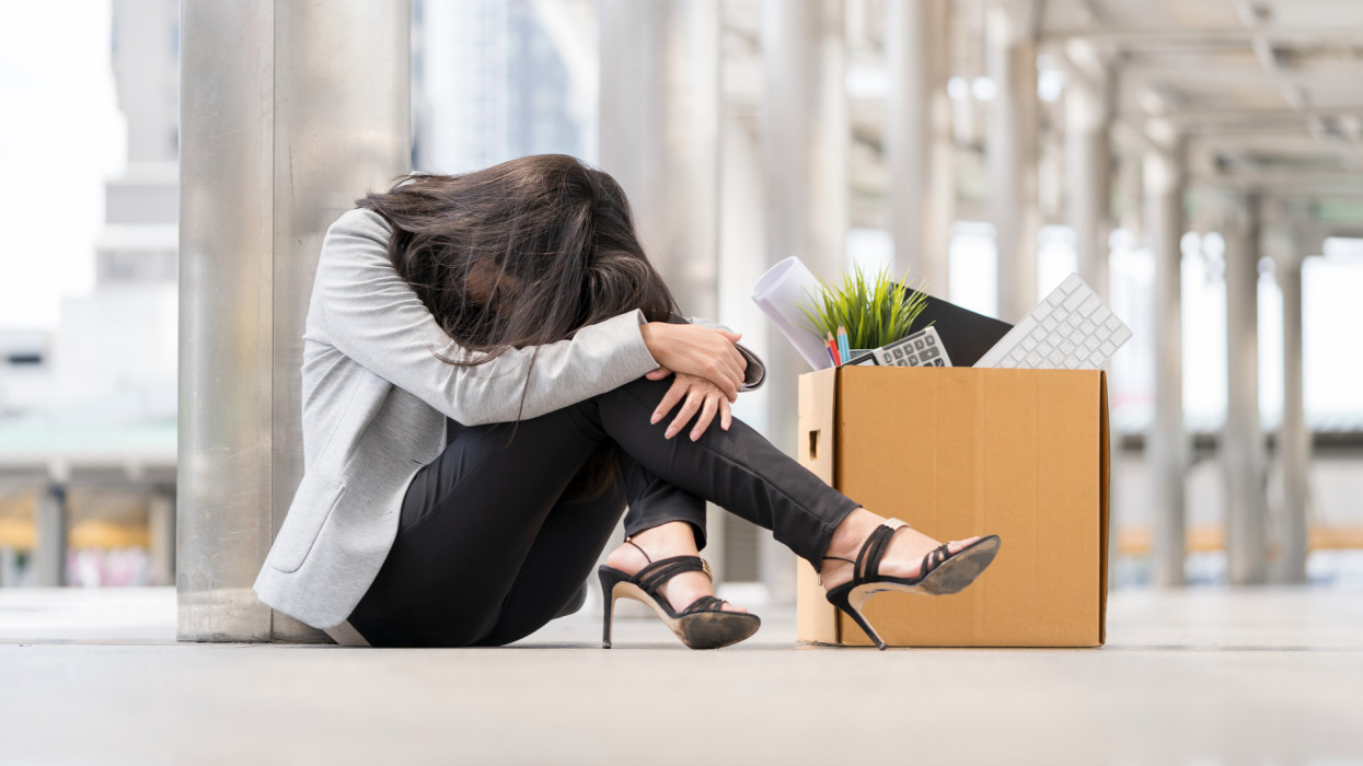 Unemployed Businesswomen with cardboard paper box sitting in city and feeling worried and sad. She got fired of business downsizing from COVID-19