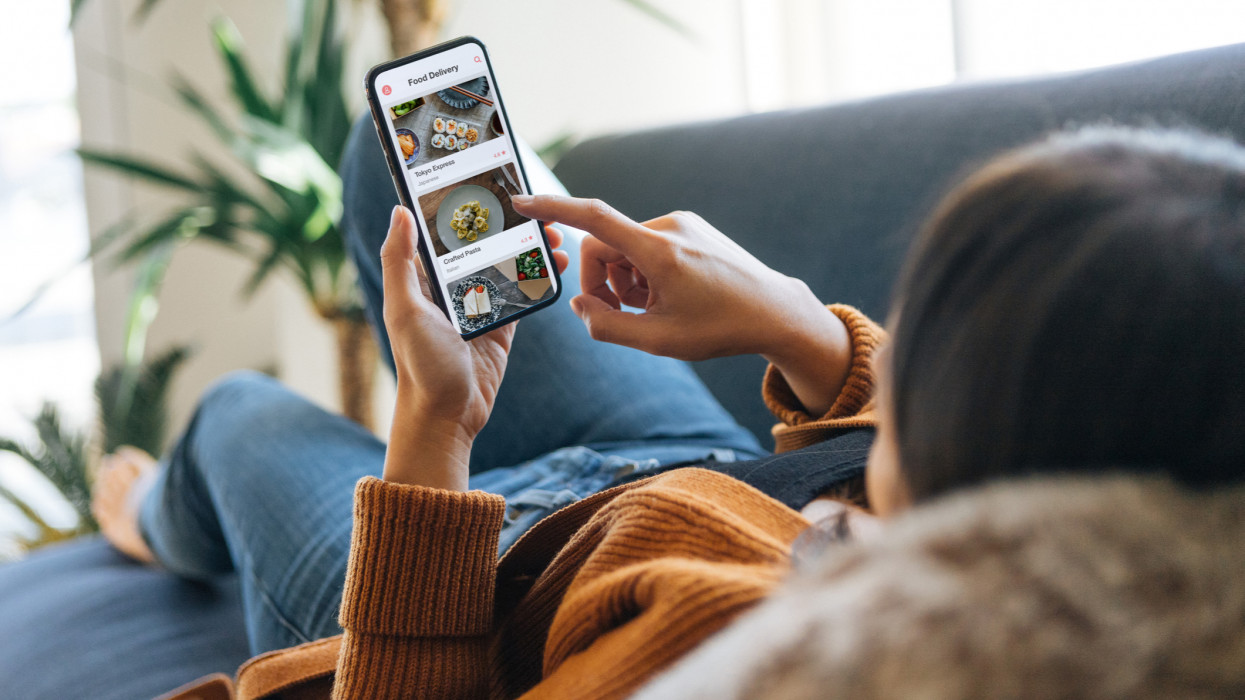 Over the shoulder view of a young woman choosing food from the menu on mobile app while lying on the couch at home.
