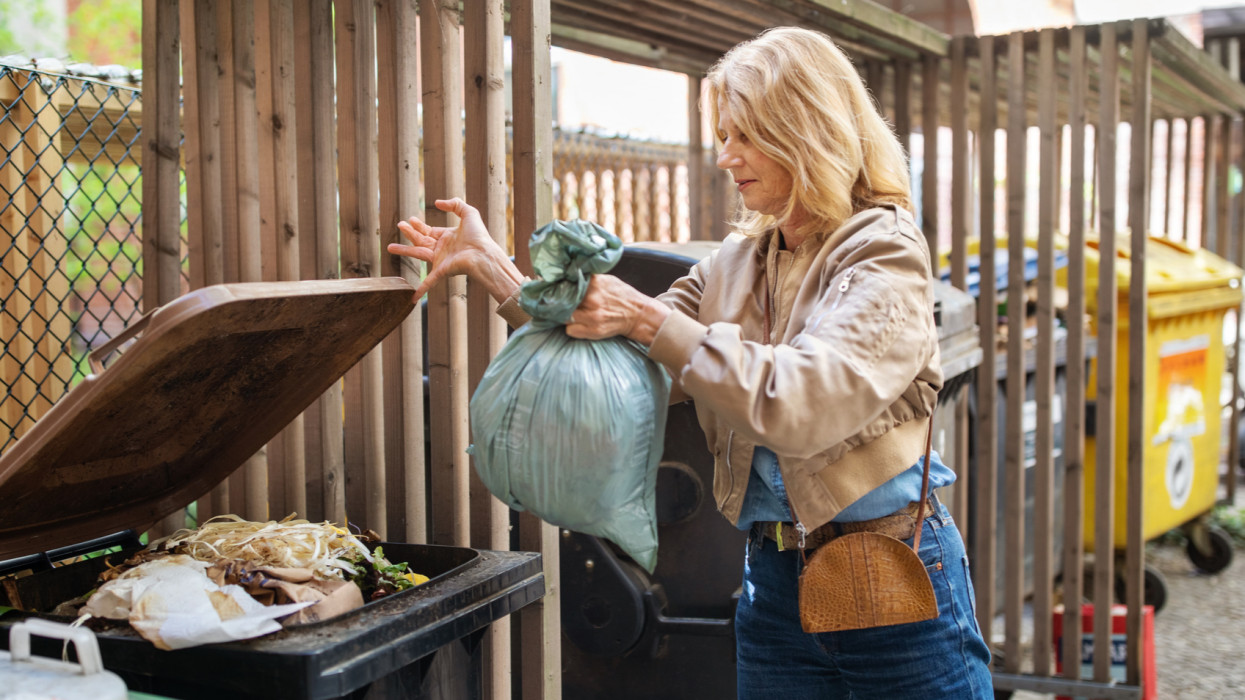 Active elderly blond woman throwing compost garbage in compost bin for recycling