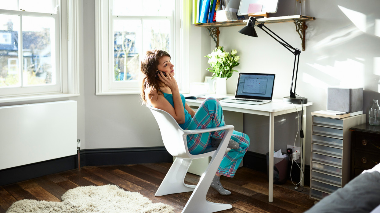 Woman in her 30s working from home, sitting at desk in bay window, listening on the phone, laptop on desk