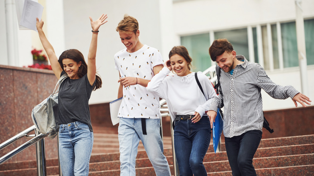 Having nice mood and good conversation. Group of young students in casual clothes near university at daytime.