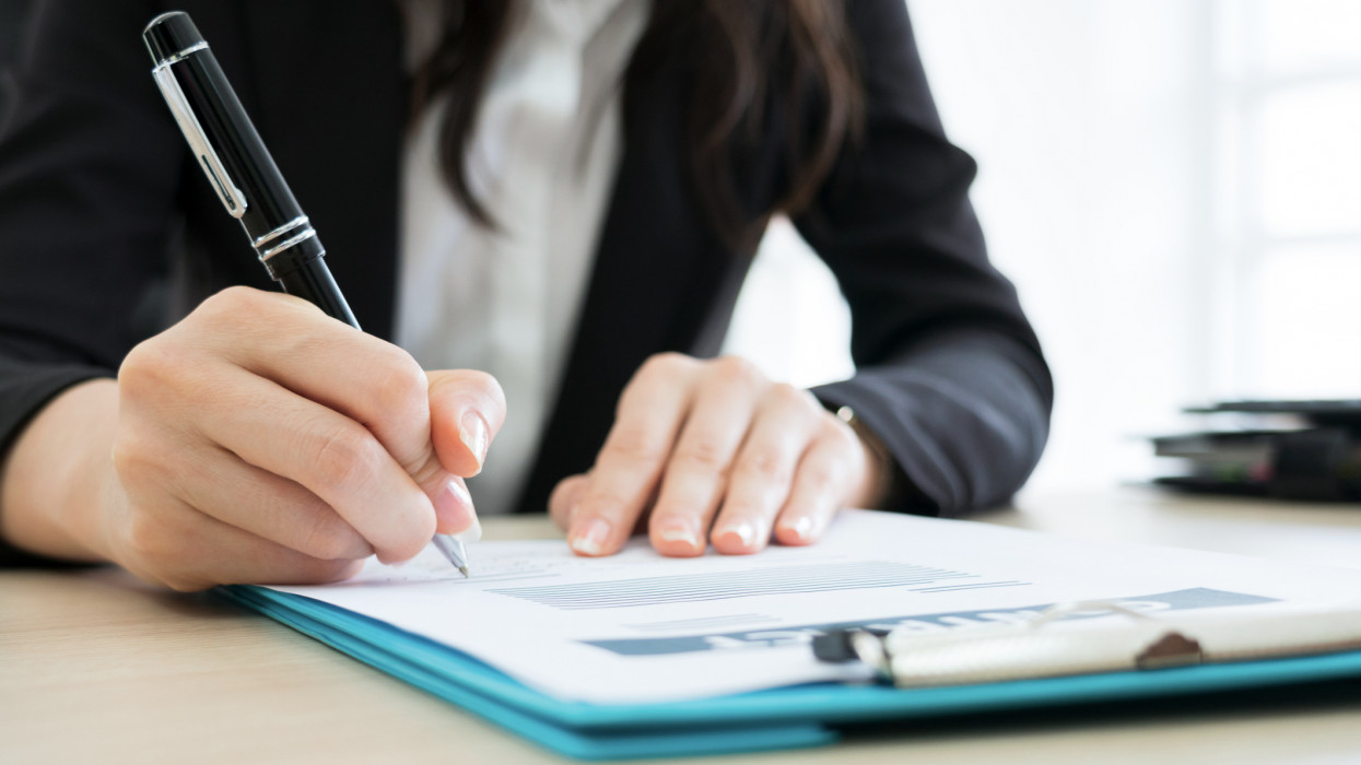 Business woman signing the contract to conclude a deal in modern office.
