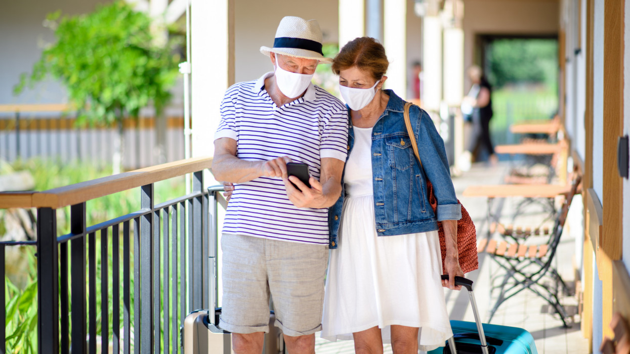 Senior couple with face masks and luggage outside apartment on holiday, back to normal concept.