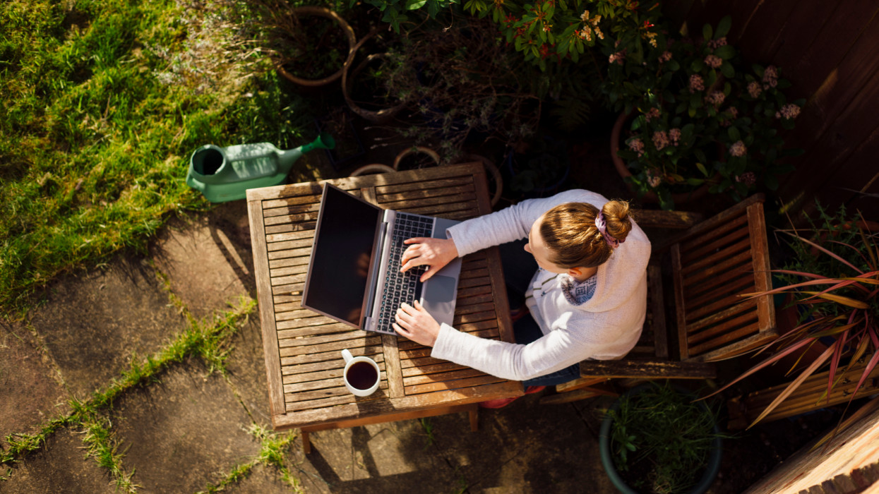 UK, Essex, Harlow, elevated view of a woman working from home in her garden using a laptop computer