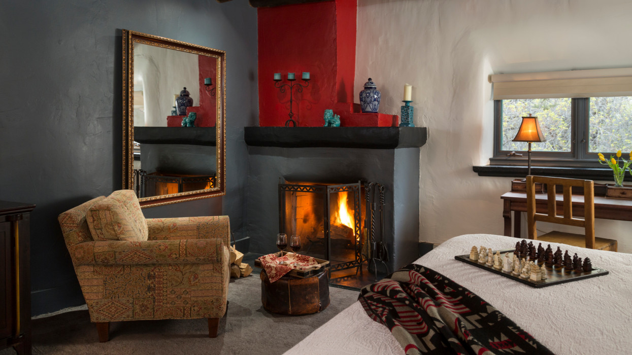 Fireplace, wine and chess set in adobe home, Turquoise Bear Inn, Santa Fe, New Mexico, USA