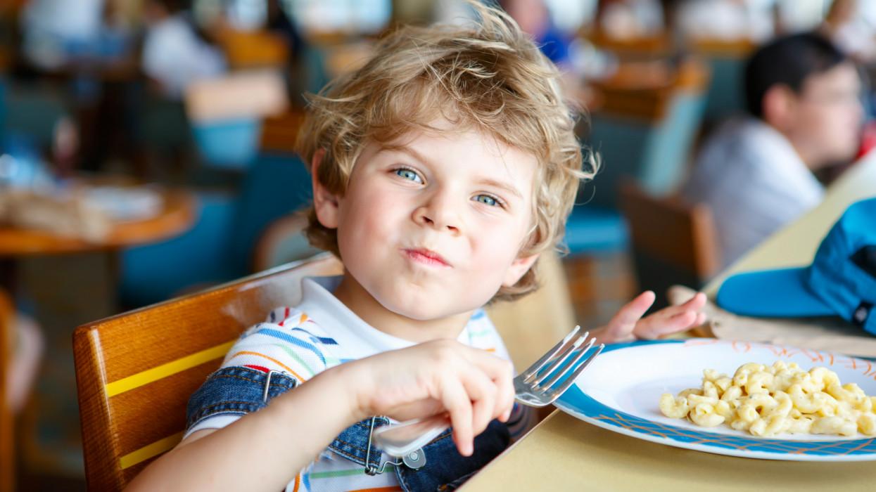 Cute healthy preschool kid boy eats pasta noodles sitting in school or nursery cafe. Happy child eating healthy organic and vegan food in restaurant. Childhood, health concept