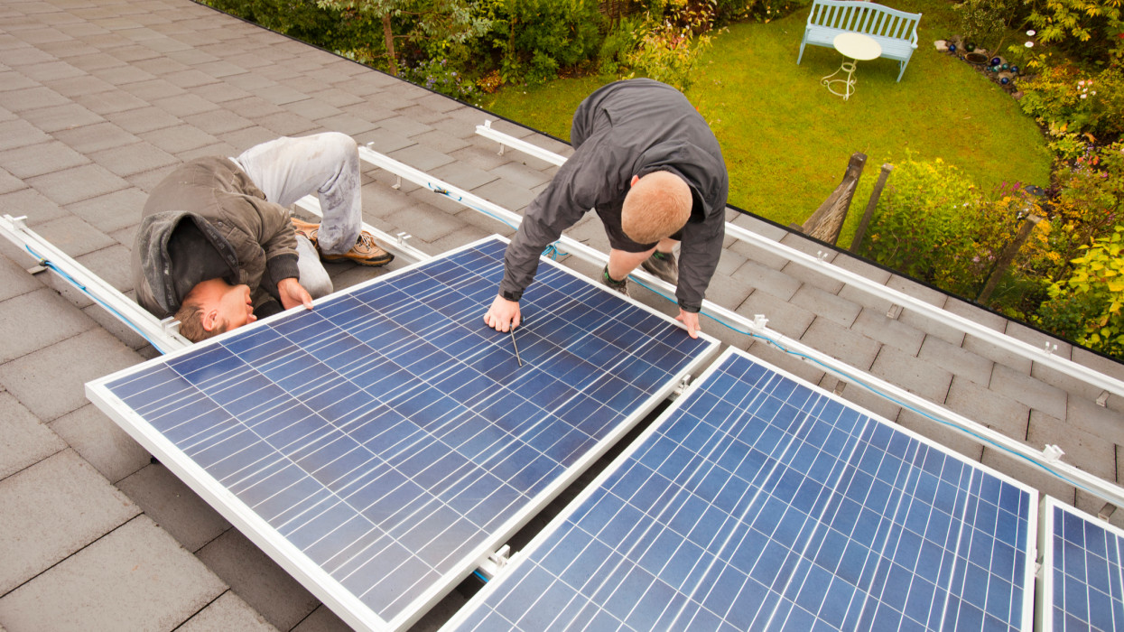 Technicians fitting solar photo voltaic panels to a house roof in Ambleside, Cumbria, UK.