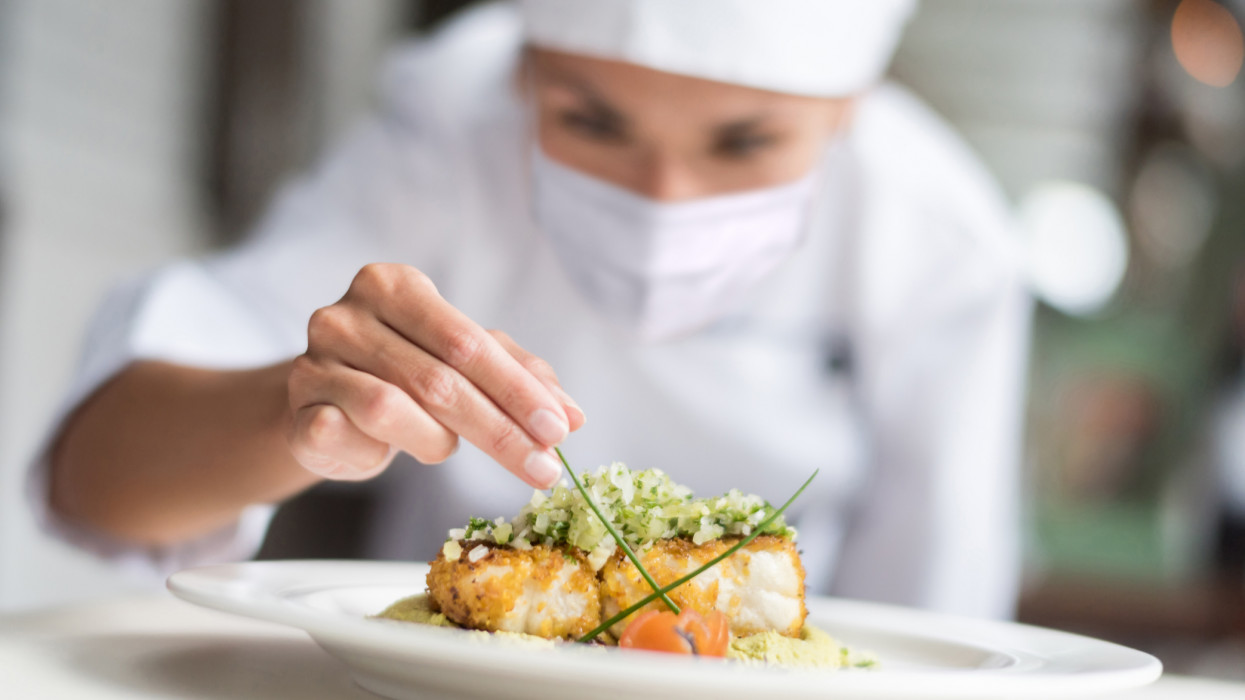 Chef decorating a plate at a restaurant while wearing a facemask during the COVID-19 pandemic – reopening of businesses concepts
