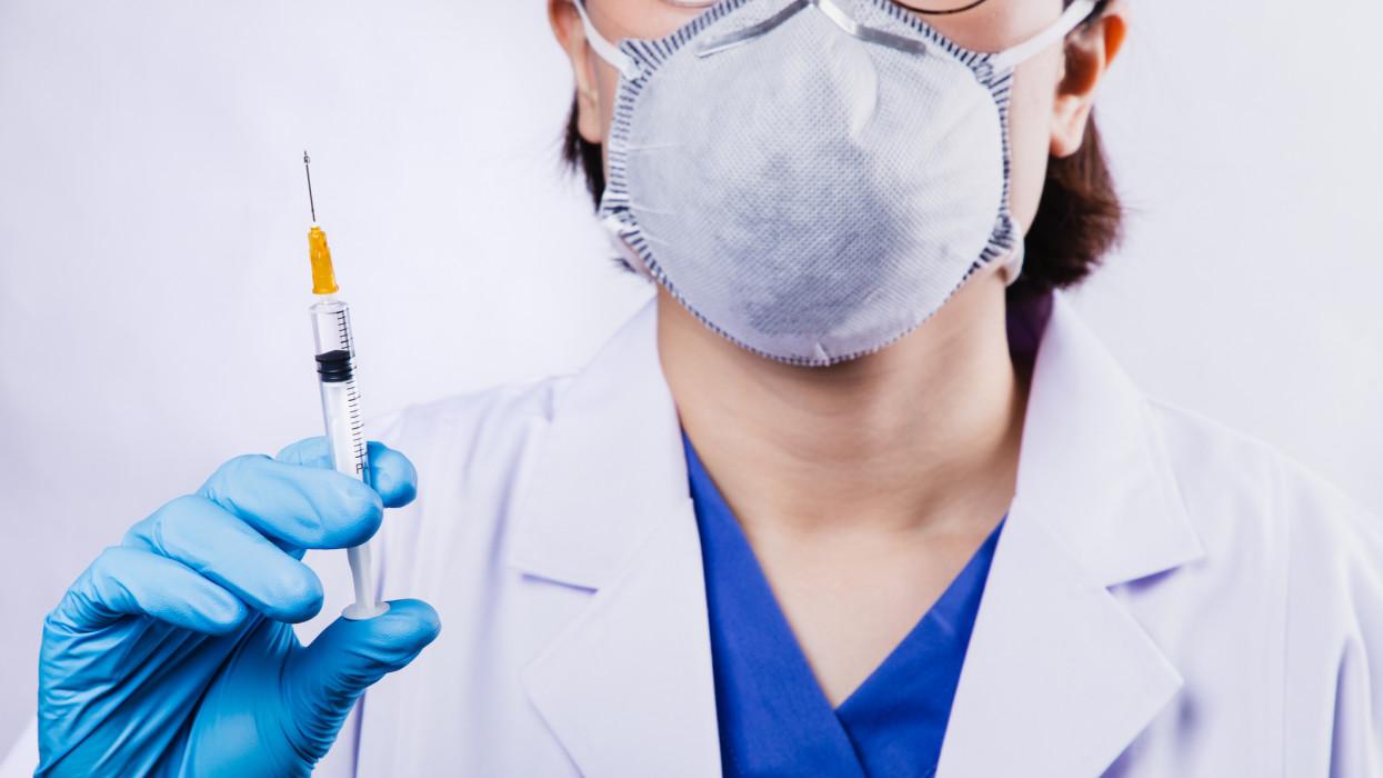 female physician wearing face mask holding a syringe