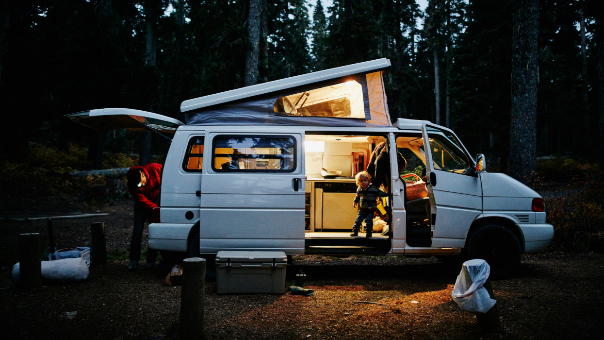 Toddler boy looking out side door of camper van parked in forest at night while father prepares camp