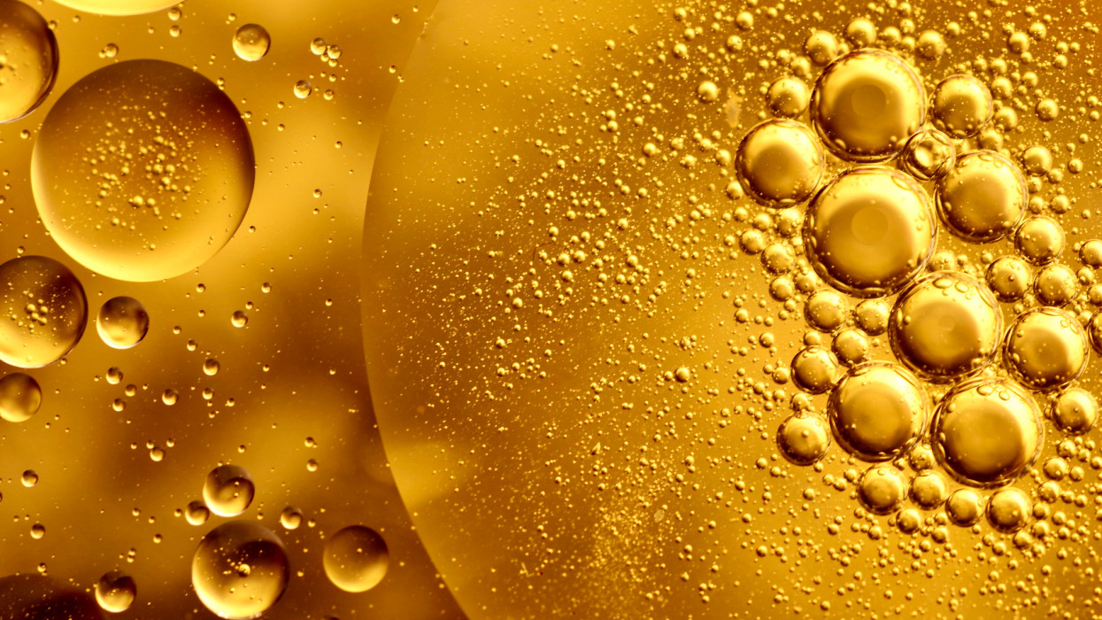 Full frame macro photography of gold-colored water and oil, forming an abstract pattern of circles and bubbles.