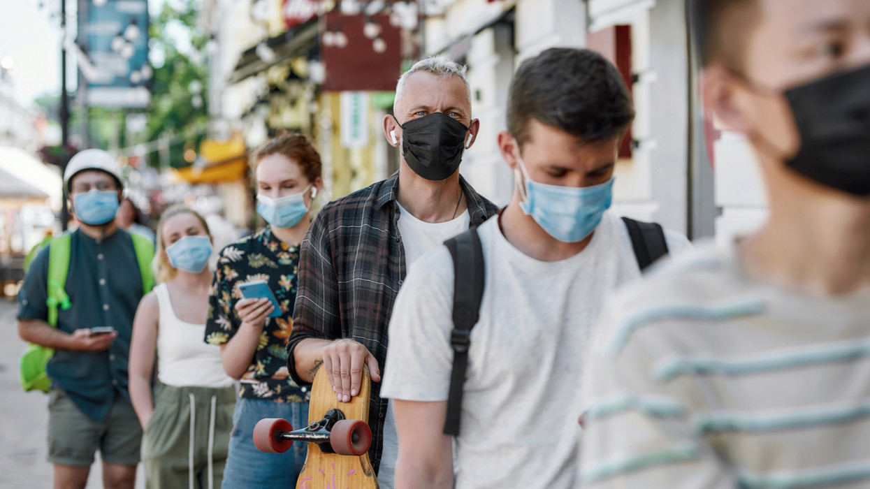 Middle aged man holding longboard, wearing mask waiting, standing in line, respecting social distancing to collect his takeaway order from the pickup point during lockdown. Selective focus