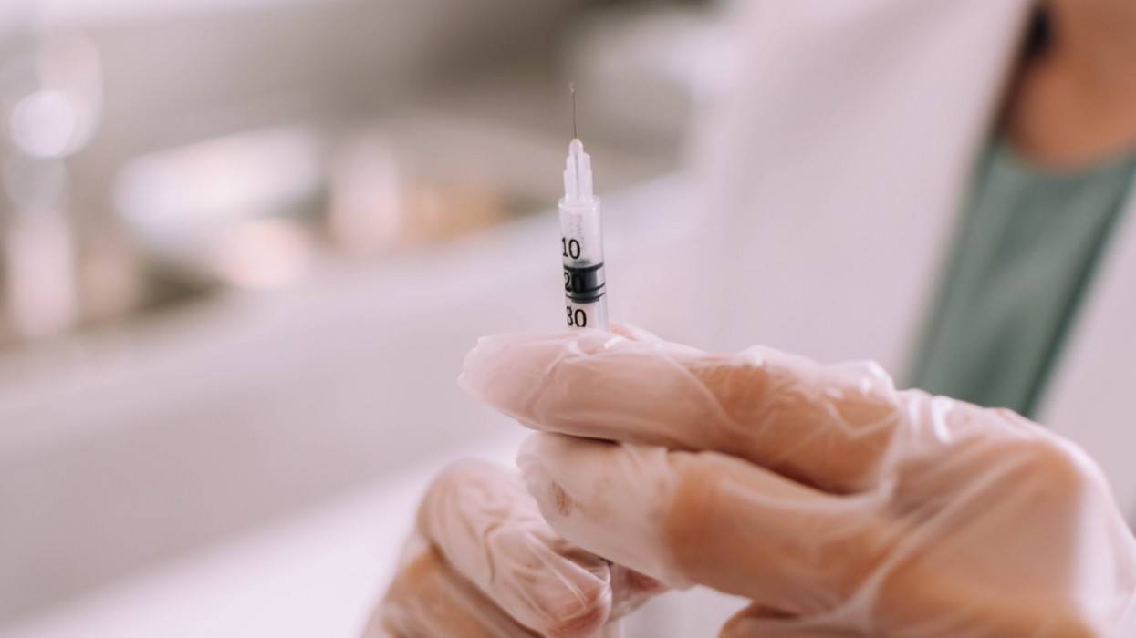 A close-up view of a young doctor holding a medical syringe in the clinic