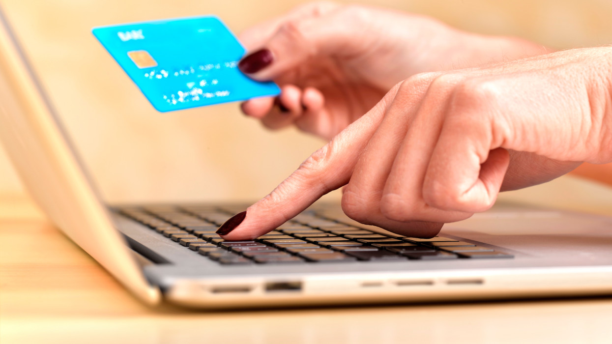 Close up of a woman at her laptop using a credit card to completer and online purchase
