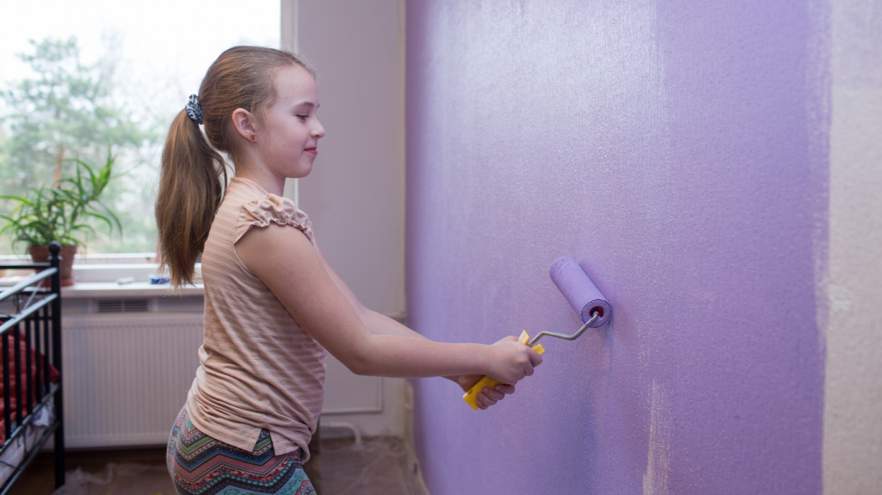 Repairs in the apartment. Girl paints the wall with ultraviolet paint - trend 2018