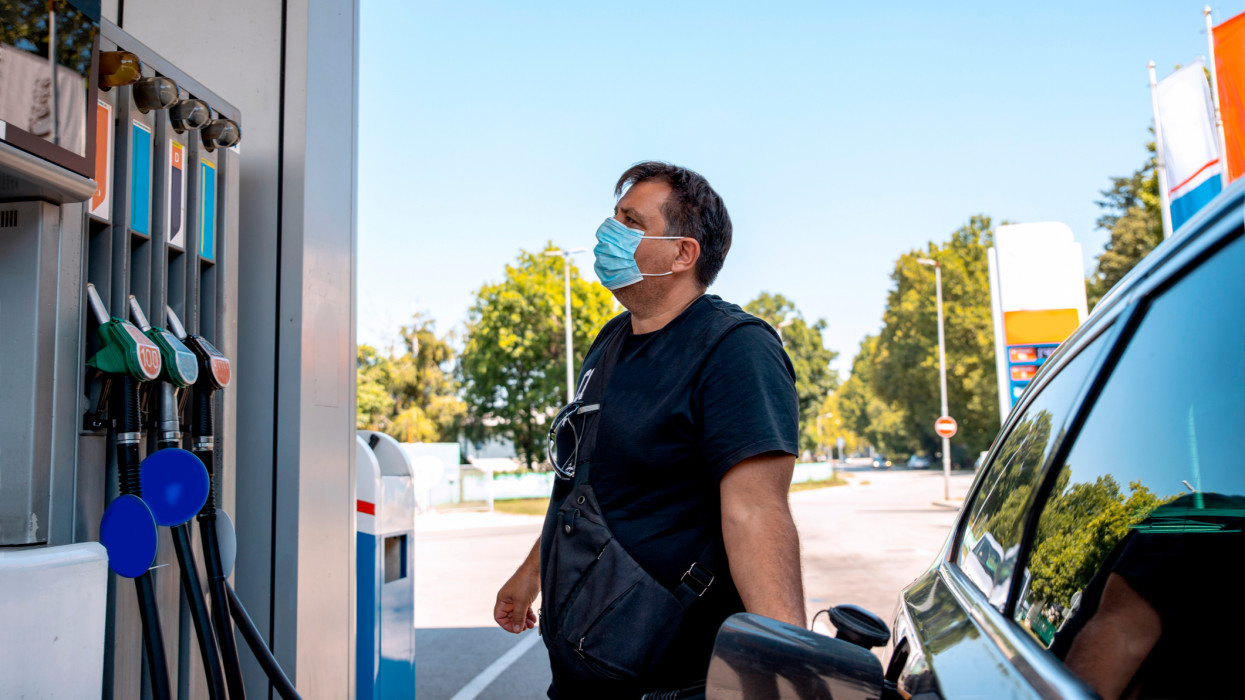Man with safety disposable face Mask on the Gas Station refueling Car, looking at fuel price