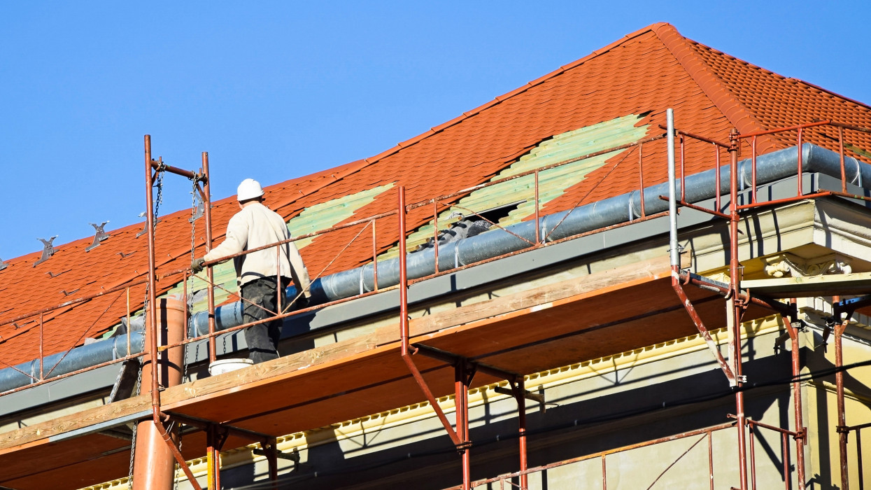 Roofer works on the roof of an old building