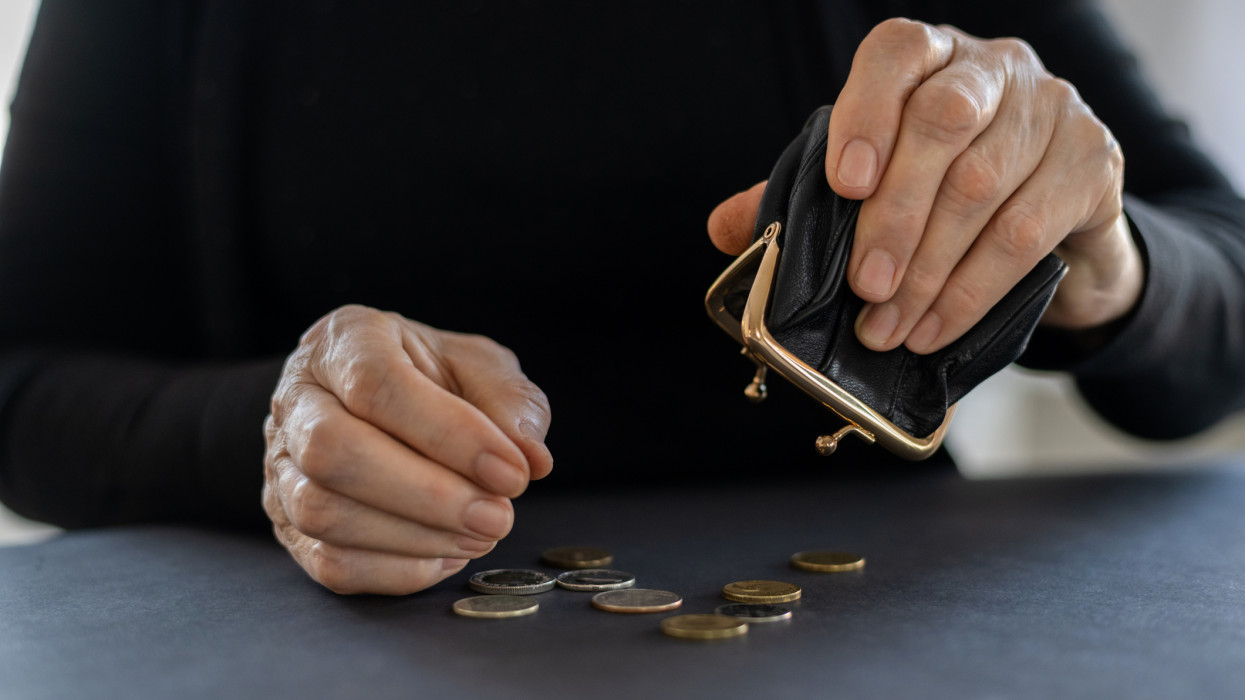 An elderly woman holds an open black empty coin purse in her hands on the lap, the concept of poverty, finance, retirement