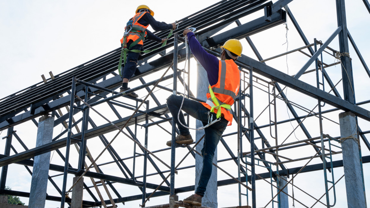 Professional worker wearing safety uniforms working at high place,Engineer and construction team working safely on scaffolding on high rise building,Construction engineering conceptual.