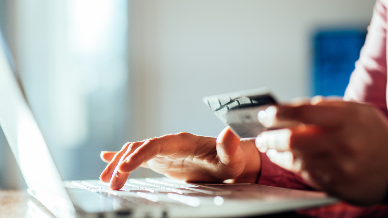 Woman shopping with a credit card at home.