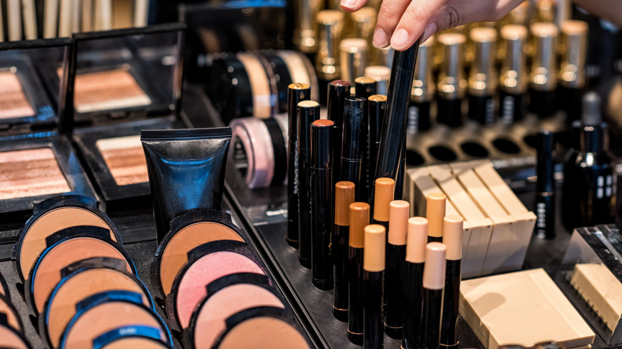 A womans hand with bracelets chooses from various shades of make-up at a high-end makeup counter.