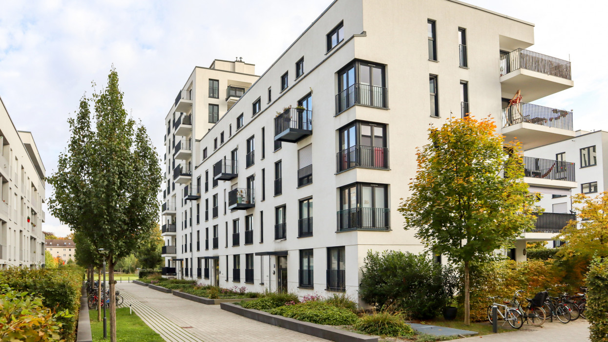 Cityscape with modern residential area, new apartment buildings and green courtyard with pavement and trees in autumn