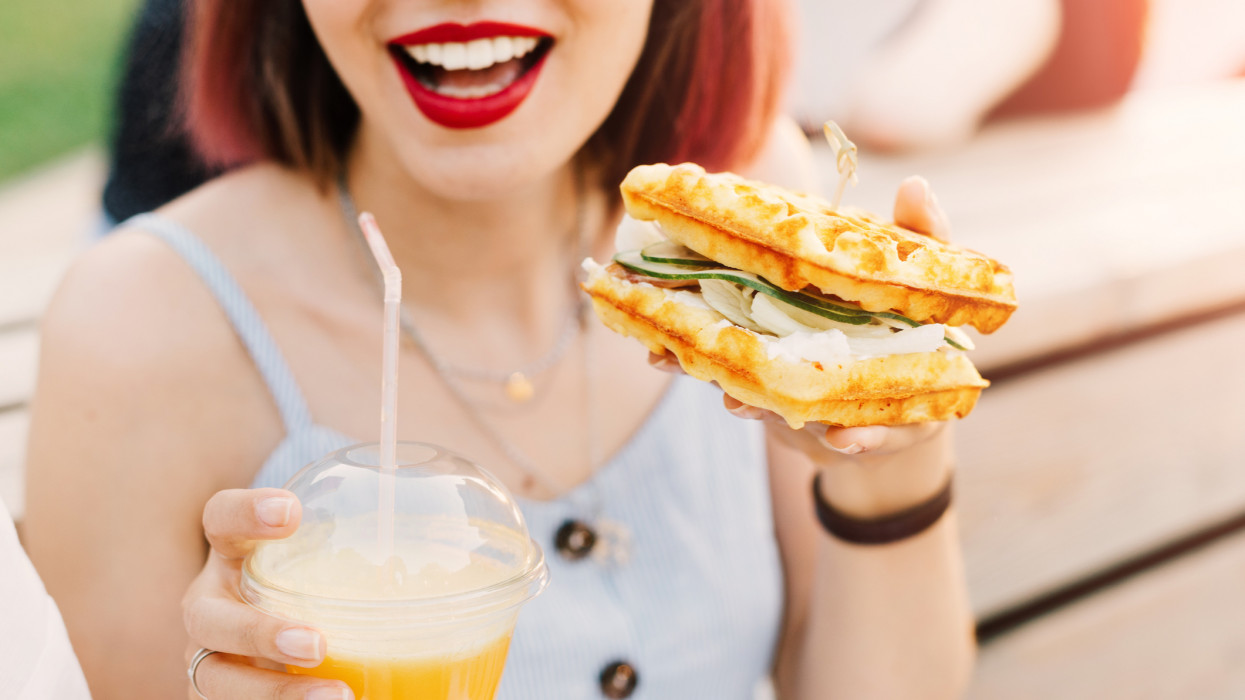 Smiling hipster woman drinks fresh juice and eats a delicious sandwich with a loaf of a checkered Viennese waffle.