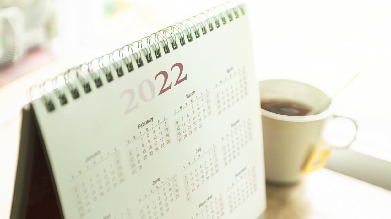 Paper desktop calendar 2022 schedule with tea cup on wooden desk