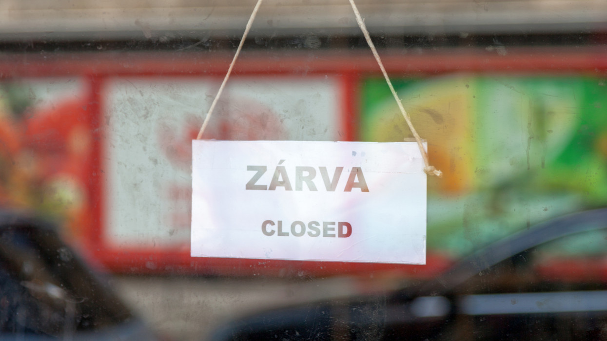 Old fashioned sign in the window of a shop saying in Hungarian Zárva, meaning in english Closed.