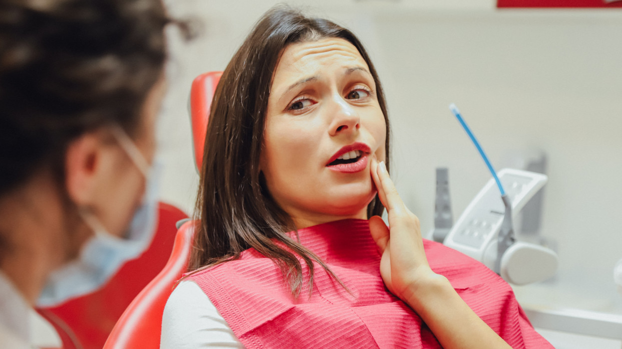 Close-up portrait of a sad young girl with a painful tooth, a doctor in office chairs, an isolated dentist office background clinic. Expressions of the human face, emotions, feelings, reactions
