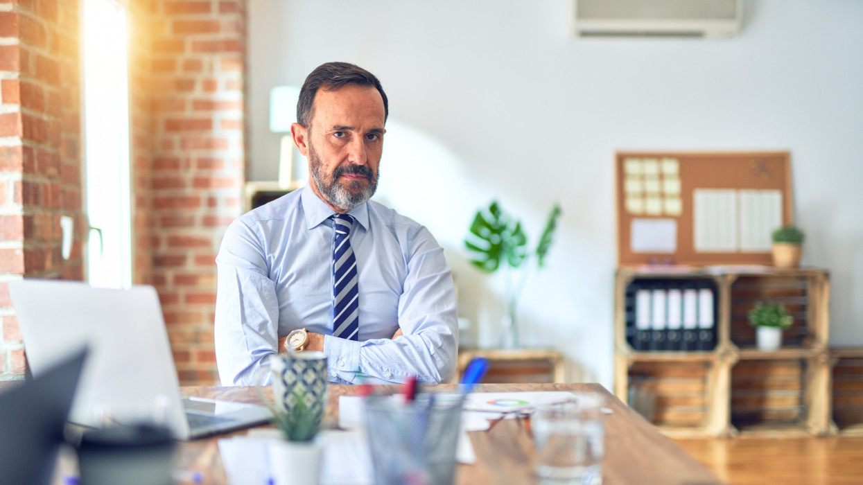 Middle age handsome businessman wearing tie sitting using laptop at the office skeptic and nervous, disapproving expression on face with crossed arms. Negative person.