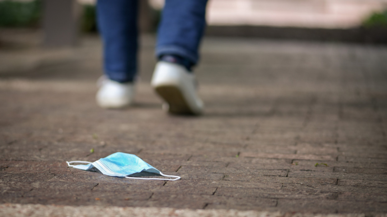 Surgical face mask for protection from Covid-19 has been dropped behind on a side walk. A Man walks away from the mask. Good for illustration of suggestions how should not behave during the pandemic of coronavirus.
