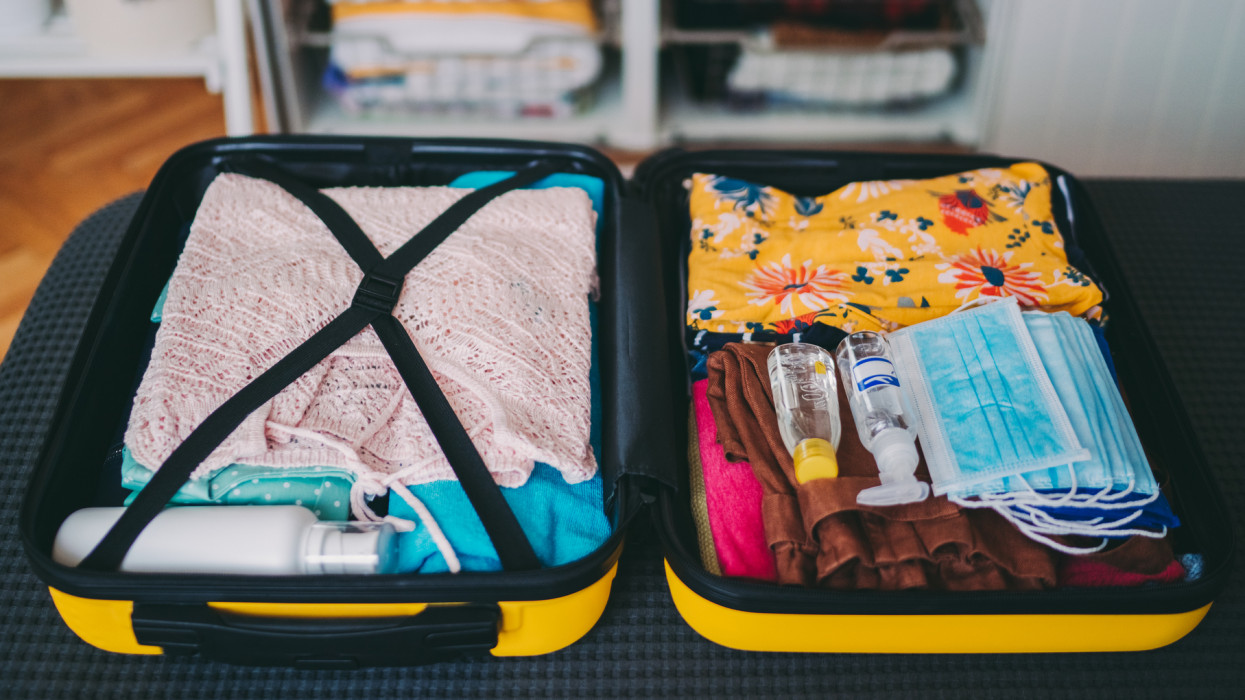 Suitcase with face masks and travel-sized antibacterial hand gels for antiseptic hand washing during travel