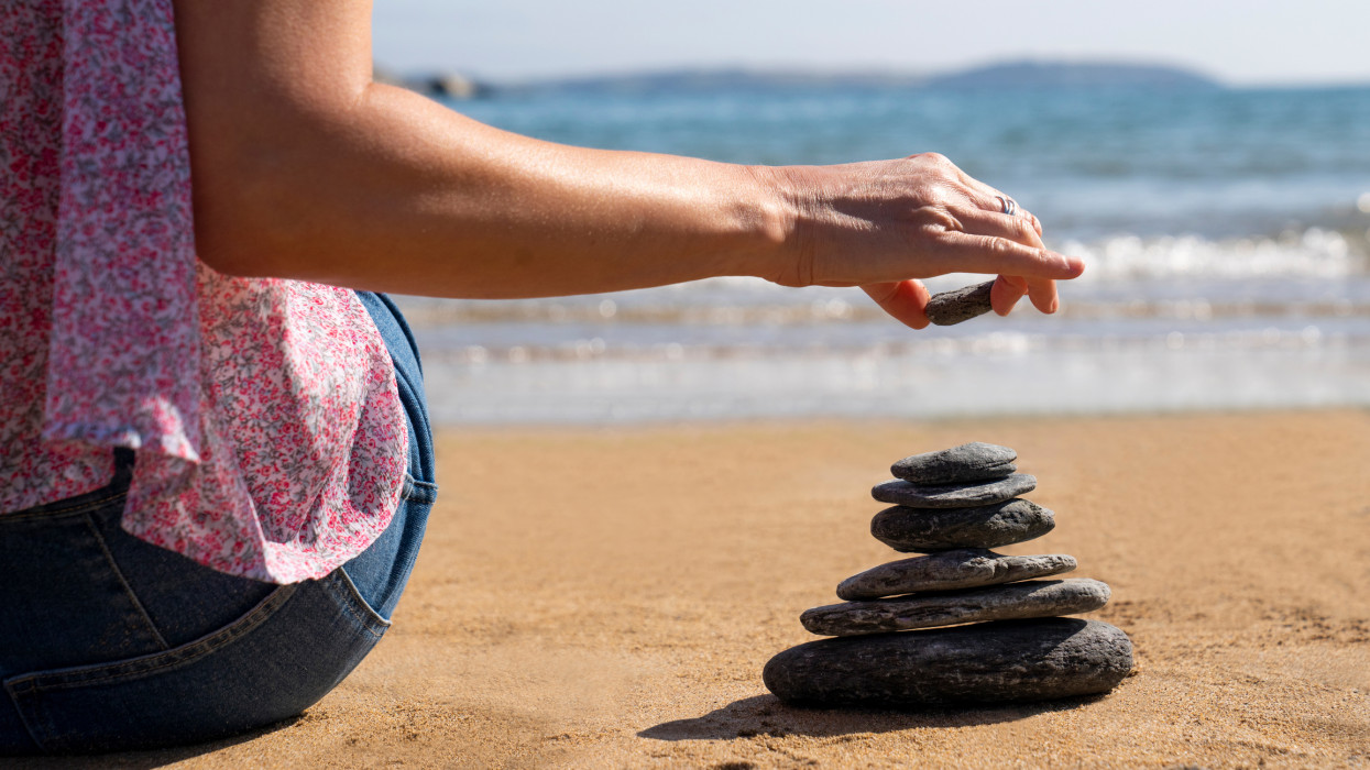 Close Up Of Relaxed Woman Stacking Stones On Peaceful Beach Vacation