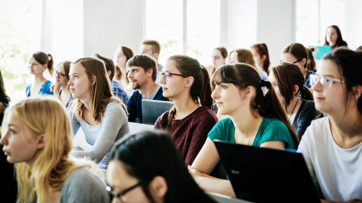 A group of students listening and concentrating on their tutor during a lecture at university.