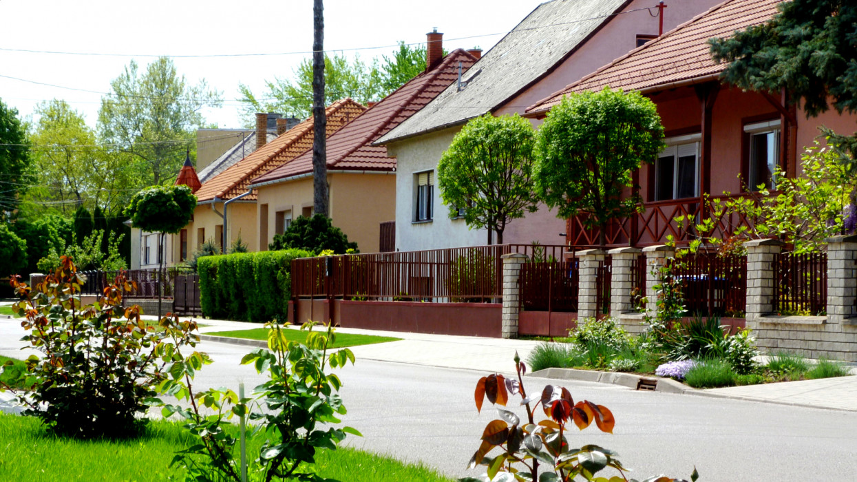 village homes along a friendly green street with lush front yards and well kept lawns, little gardens, rose bushes and new red clay roofs. home ownership concept. European village.