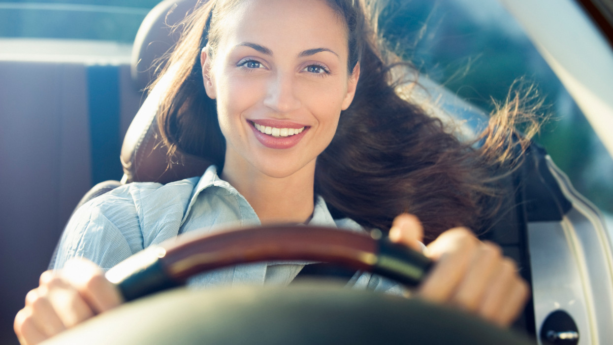 Portrait of a smiling young brunette woman 22 years old with brown eyes driving a convertible car with hands on the steering wheel and long hair blown by wind, she has her belt fasten and wears a blue shirt, view through the windscreen, France, Nice