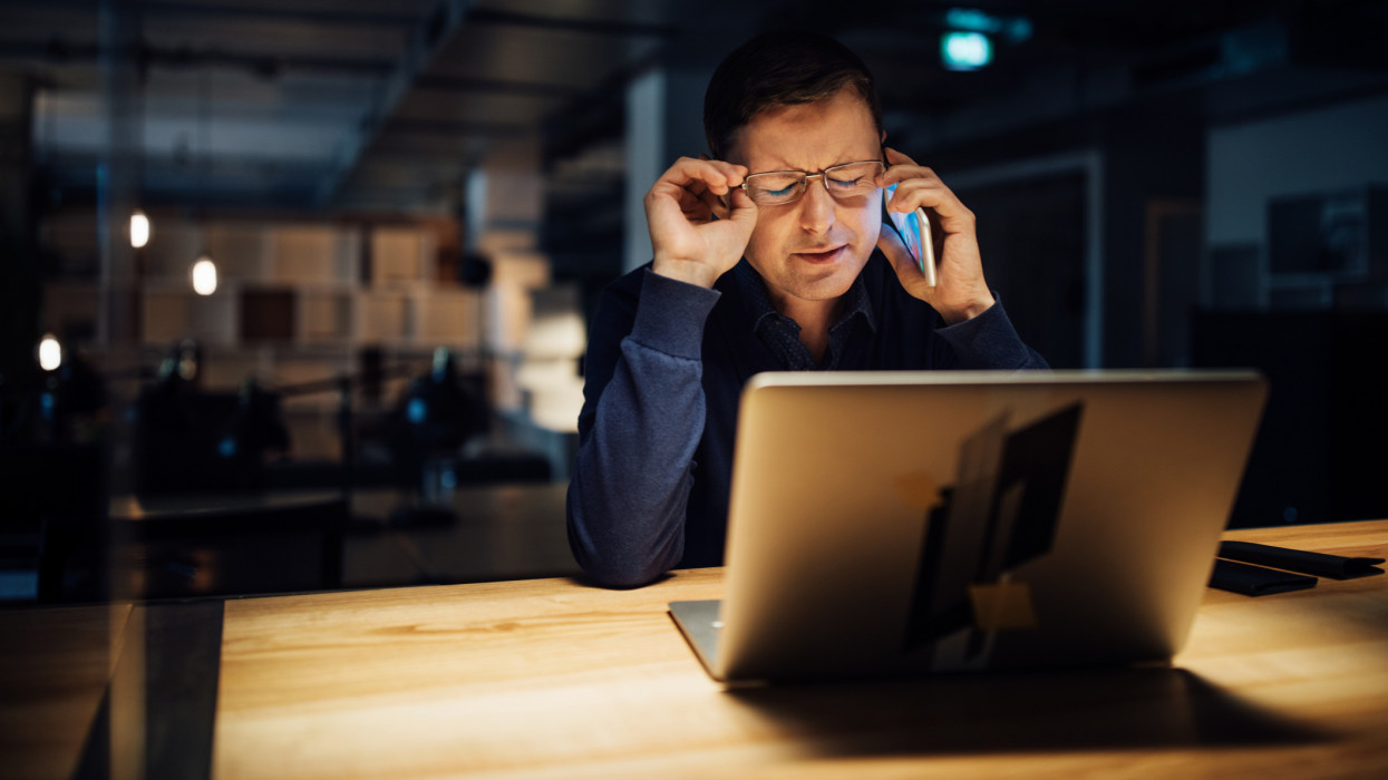 Businessman talking on mobile phone working late on laptop while sitting at desk in office