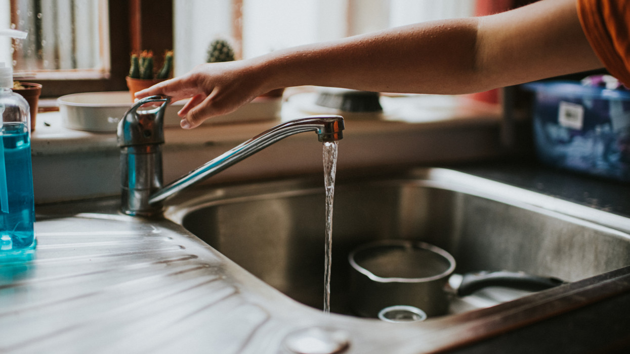 Hand reaching across a sink below a window, to press down tap to turn off the running water. Pot and bowl sit in the sink. Antibacterial hand soap sits off to the side.