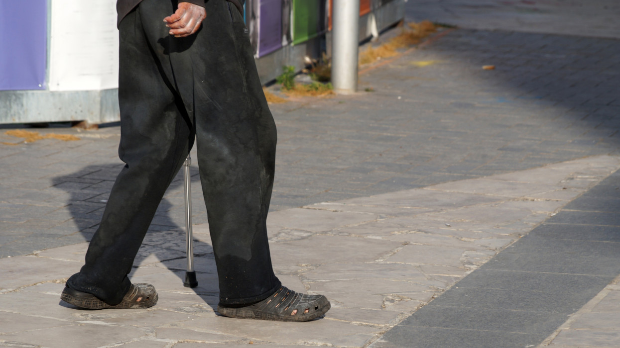 an elderly poor man walks with a cane down the street in dirty clothes, bottom view