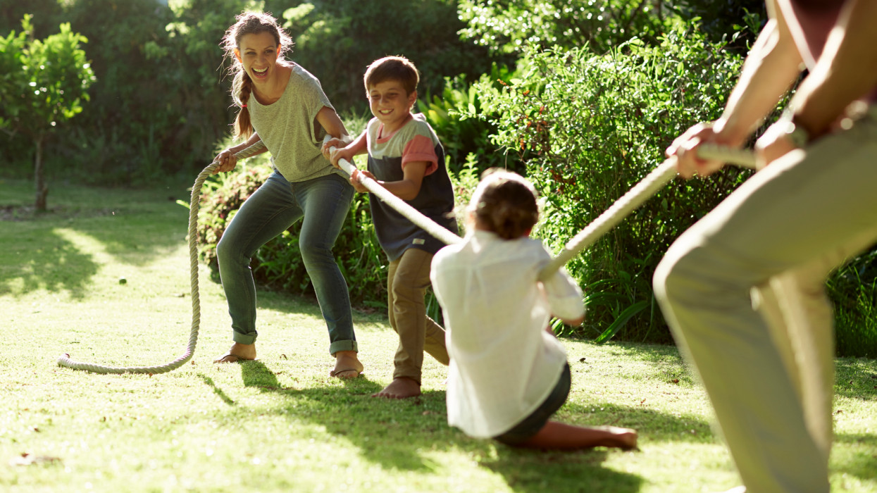 Two generation family playing tug-of-war in park