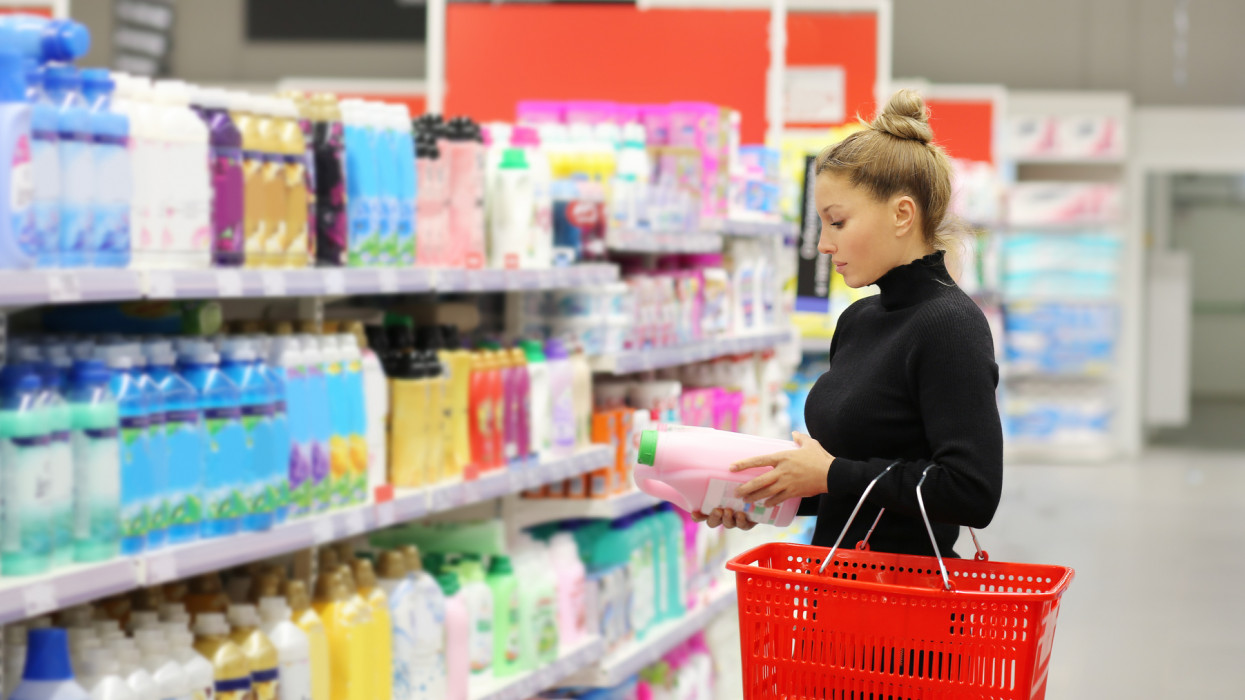 Woman shopping in supermarket reading product information.(shampoo, soap, shower gel,)