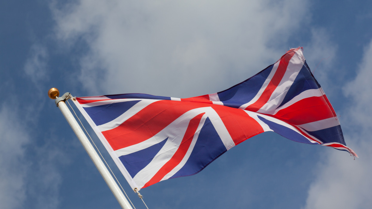 The iconic Union Jack flag flies against a blue sky in Ipswich, Eastern England.