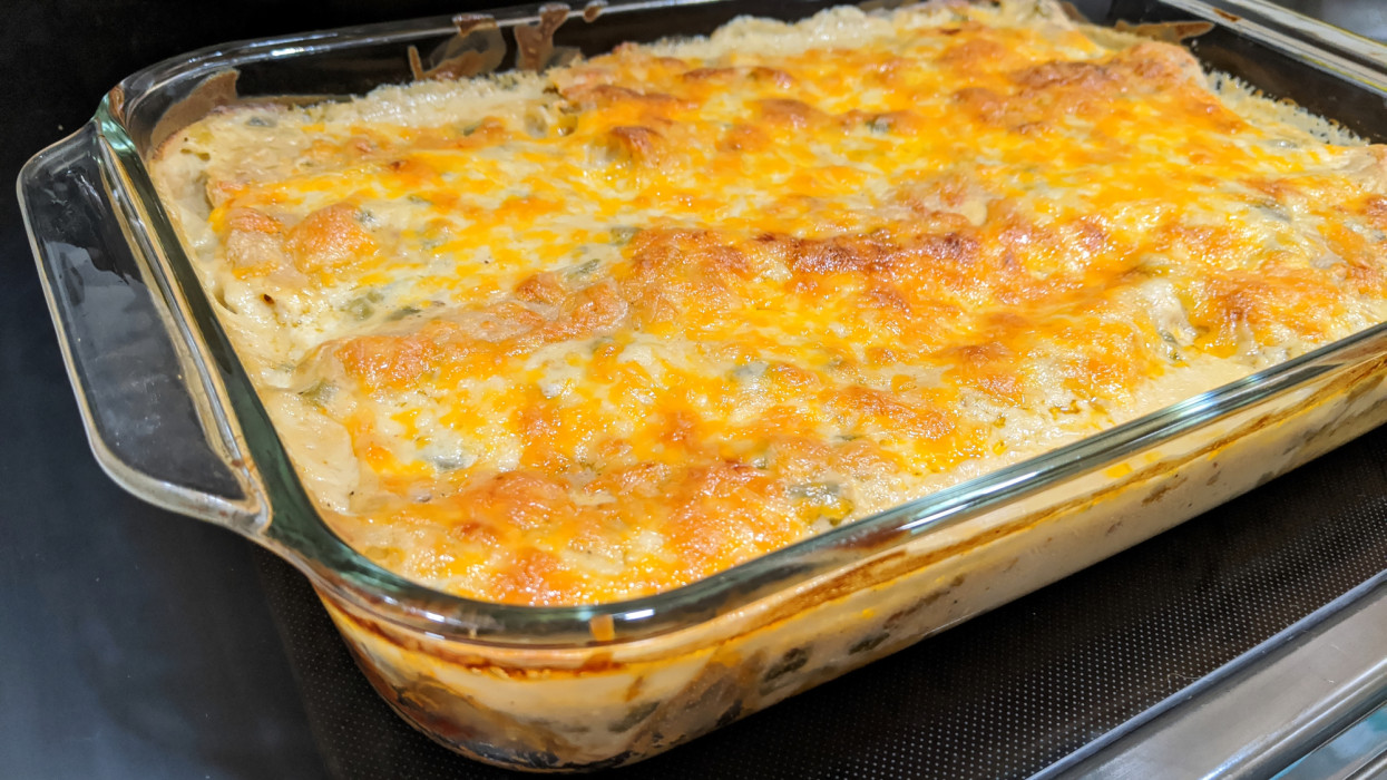 Baking dish of enchiladas covered in melted cheese