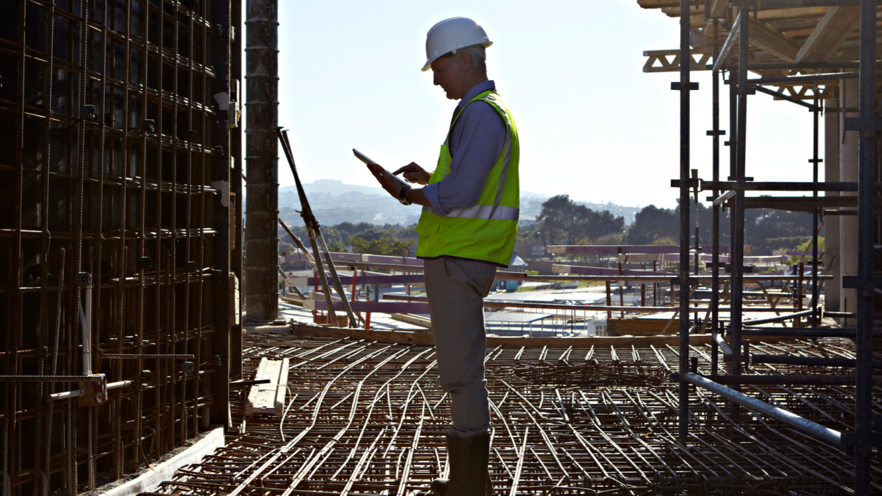 Architect, aged 52, using a tablet computer to check data while standing on a network of reinforcing bars laid down to become a reinforced concrete floor on a large building site