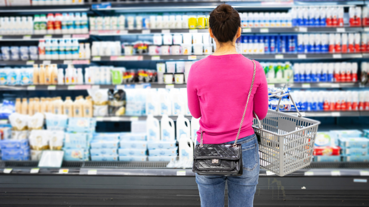 female buy dairy product in supermarket