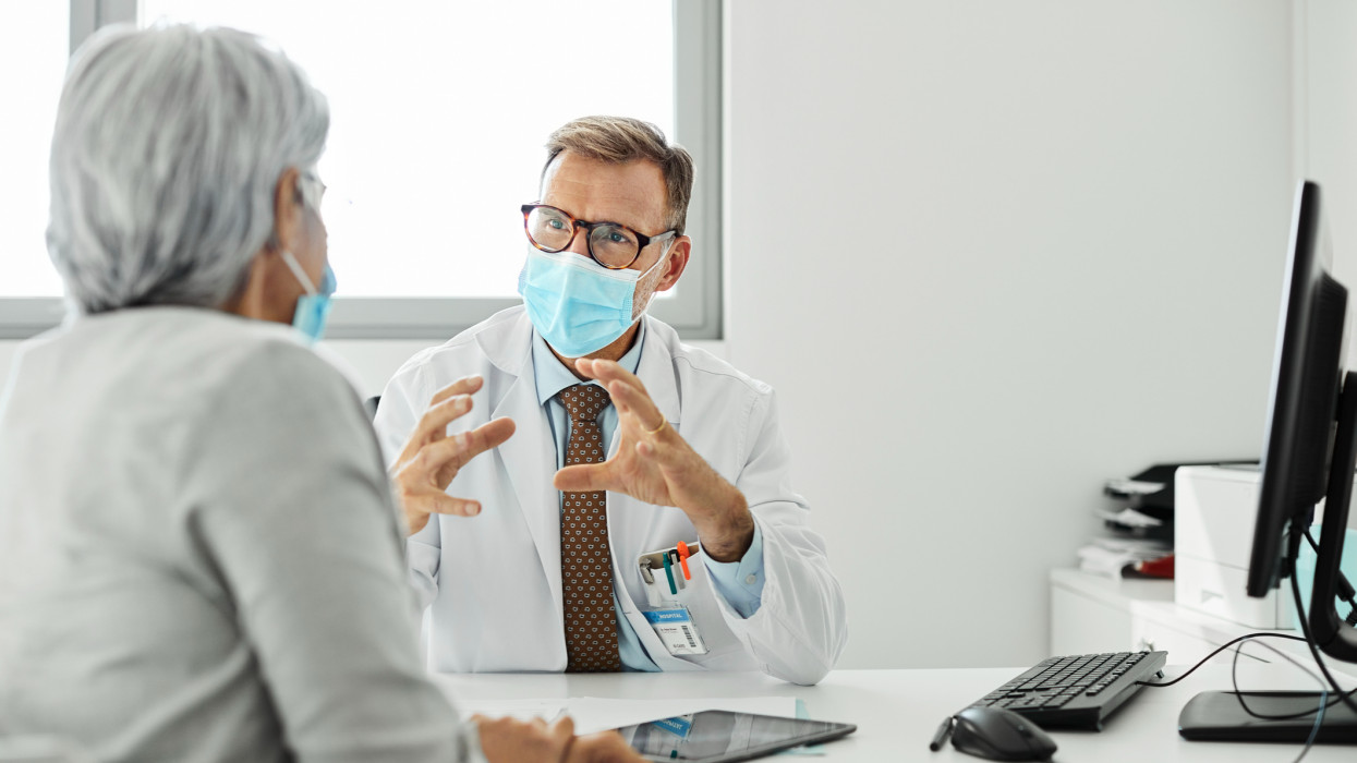 Doctor discussing with female patient during COVID-19. Male medical professional is explaining woman while sitting at desk. They are wearing protective face masks in clinic.